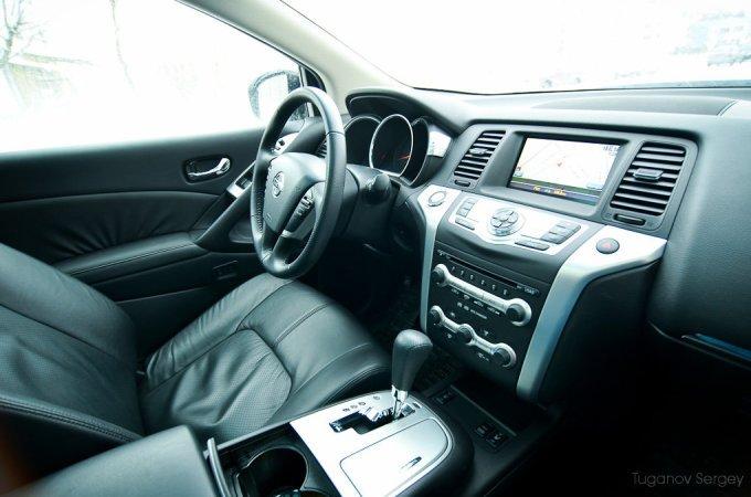 В салоне топовой модификации Мурано много кожи. Она почти повсюду: и на панели, и на дверях, и на сиденьях, и на руле. А вот выпирающая центральная консоль, увы, сделана из жесткой, но аккуратной пластмассы.