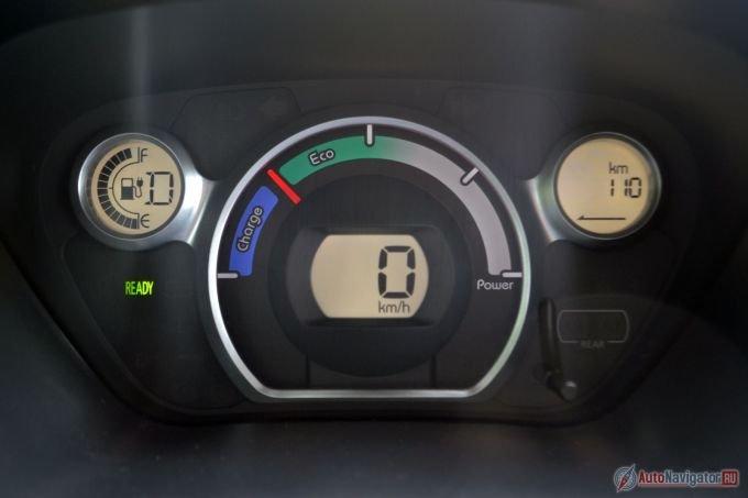 Скорость высвечивается в цифровом виде на центральном экране, слева расположен индикатор заряда, справа – бортовой компьютер, который на данной фотографии показывает запас хода. Основной стрелочный прибор – эконометр. Чем правее стрелка, тем больше энергии тратится, в синюю зону стрелка уходит только при рекуперативном торможении. Надпись «Ready» загорается, когда машина «заведена»