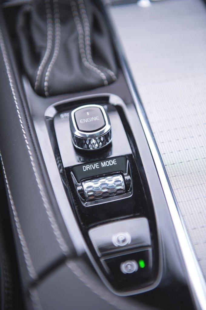 Кроссовер XC90 оснащен бесключевой системой запуска мотора, однако двигатель заводится и глушится не банальной кнопкой, а интересным 2-позиционным переключателем, который можно поворачивать влево и вправо. Чуть ниже этого «джойстика» размещено хромированное колесико, отвечающее за выбор режимов работы подвески, КПП и силового агрегата