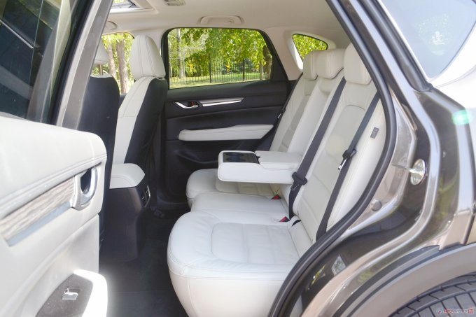 Сзади CX-5 не рекордсмен по простору для ног, но сидеть очень удобно, наклон спинки регулируется в небольшом диапазоне, есть подстаканники, подлокотник, дефлекторы обдува, карманы в спинках передних кресел и в дверях, хорошая шумоизоляция, много места для ступней под передними сиденьями